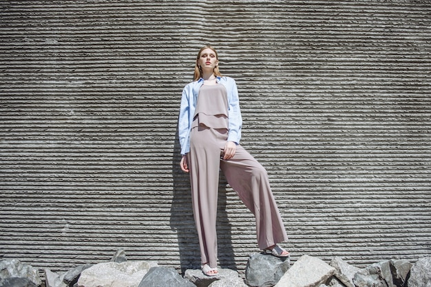 패션 벽 배경에 포즈를 취하는 아름다운 여성 모델