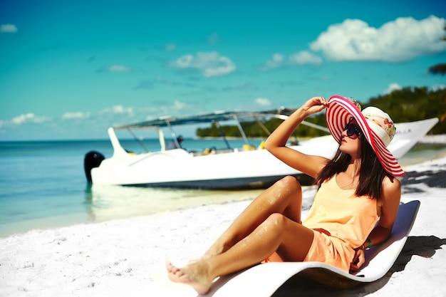 Красивая женщина модель загорать на шезлонге в белом бикини в красочной шляпе от солнца за синей летней водой океана