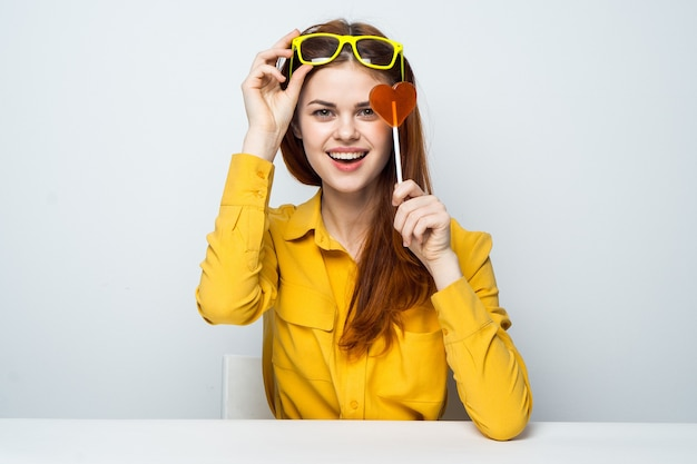 Модель красивой женщины с леденцом на палочке в форме сердца за столом в желтой рубашке позирует