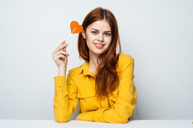 Модель красивой женщины с леденцом на палочке сердца за столом