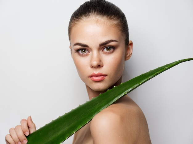Beautiful woman model with aloe leaf in hand clean skin cosmetology model natural look