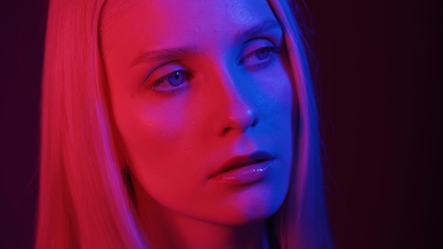 Beautiful woman model with blue eyes posing in neon light close-up. fashion photography concept. 4k uhd