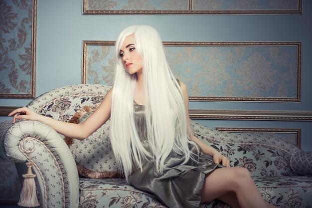 Модель красивой женщины с длинными платиновыми белыми волосами в стене интерьера