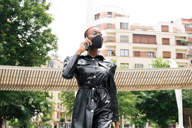コロナウイルスパンデミックコビッド19が路上で彼女のビジネスの世話をしている彼女の携帯電話で話しているため、マスクを持つ美しい女性モデル