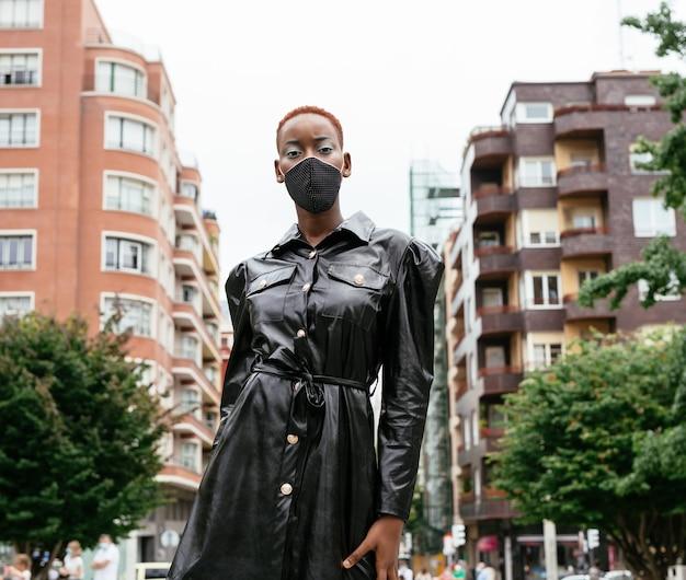 코로나 바이러스 전염병 코로나 19로 인해 마스크가있는 아름다운 여자 모델이 멋진 검은 드레스로 거리에서 스타일을 걷고 있습니다.