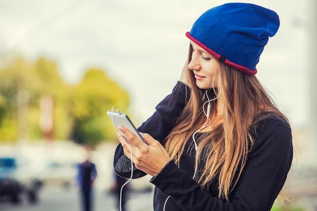 通りに電話とヘッドフォンを持つ美しい女性モデル。コミュニケーション、音楽、ポートレート、リスニング、スタイル