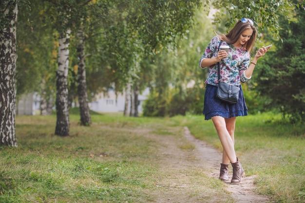 公園で持ち帰り用のコーヒーと電話を持つ美しい女性モデル。スタイル、カジュアル、ドリンク、ハッピー、サニー