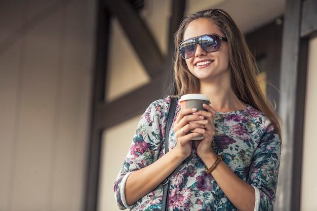路上でテイクアウトコーヒーと美しい女性モデル。スタイル、カジュアル、レストラン、ドリンク、ペストリー