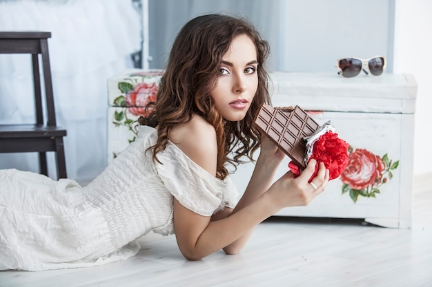 Beautiful woman model with tiles of dark chocolate in hands against bedroom interior
