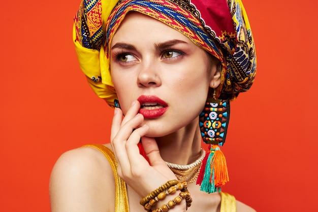 아름 다운 여자 여러 가지 빛깔된 목도리 민족 아프리카 스타일 장식 빨간색 배경입니다. 고품질 사진