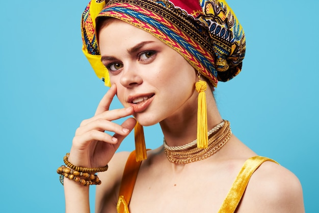 Beautiful woman in multicolored turban attractive look jewelry smile isolated background