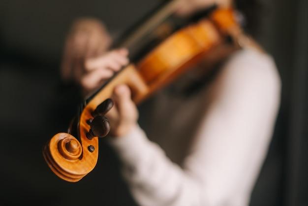 Красивая женщина-музыкант играет на скрипке в своем доме крупным планом. лица женщины не видно.