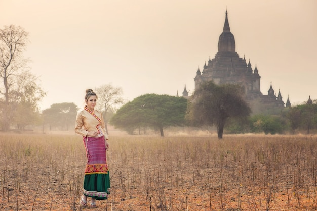 Beautiful woman in myanmar traditional costume posing in the field