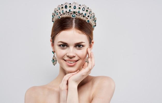 Плечи красивой женщины нагие и ювелирные изделия принцессы драгоценностей диадемы. фото высокого качества