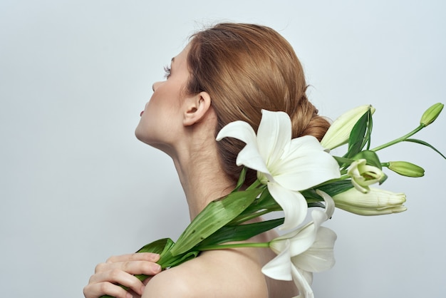 美しい女性の裸の肩の花束の花の化粧品きれいな肌