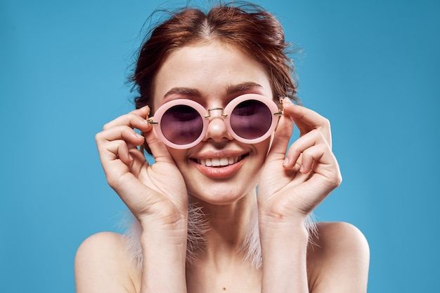 Красивая женщина обнаженные плечи пушистые серьги солнцезащитные очки аксессуары макияж