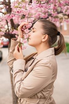 桜の木の近くの美しい女性。街の通りの木々にピンクの花が咲きます。周りに木が咲きます。春の時間の概念