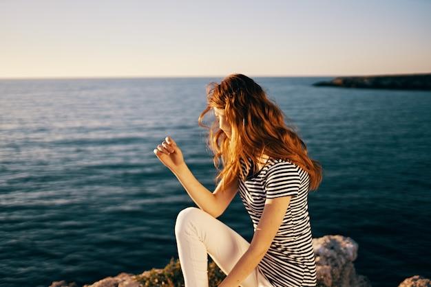 日没の夏のtシャツの空で海の近くの美しい女性