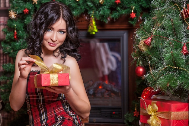 Beautiful woman in new year's style with a gift in hands on surface of christmas tree
