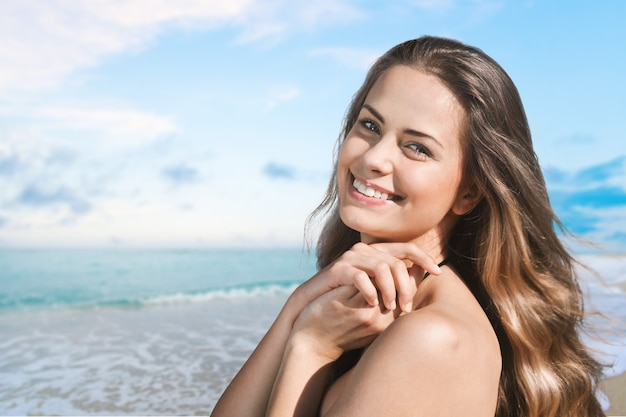 Beautiful woman  over ocean background. sun tanning. skin care and protection. vacation