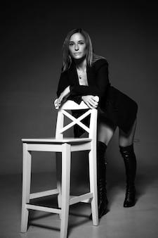 Красивая женщина кавказской национальности позирует, сидя на стуле в черной куртке и нижнем белье