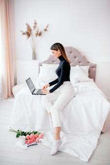 ヨーロッパの外観の美しい女性が自宅の明るい部屋のコンピューター、オンライン作業で動作します