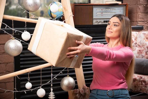 自宅でギフトボックスを提供する美しい女性