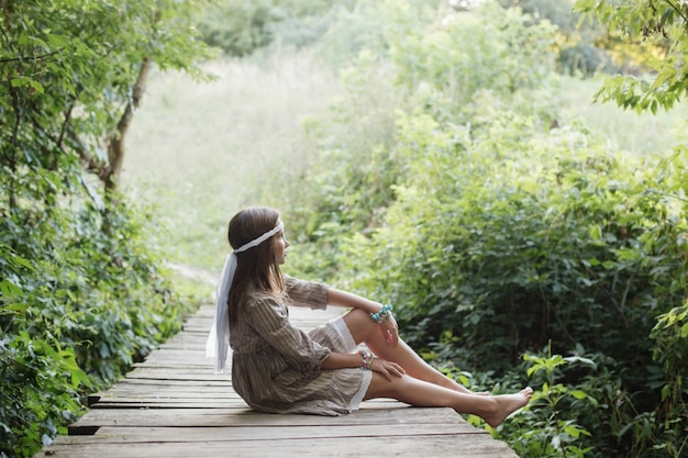 Beautiful woman on old wooden bridge in forest