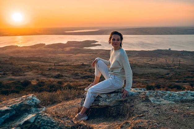 Красивая женщина на скале на закате.