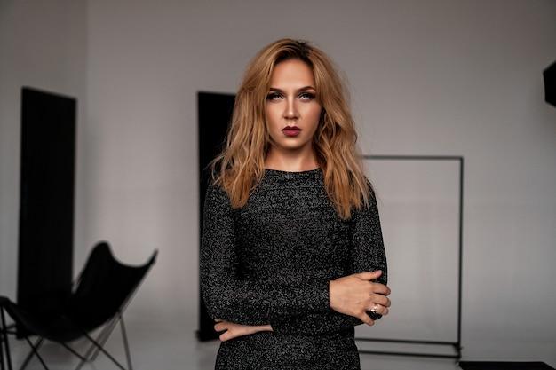 黒の古典的なドレスの美しい女性がスタジオでポーズします。豪華なスタイルの写真。