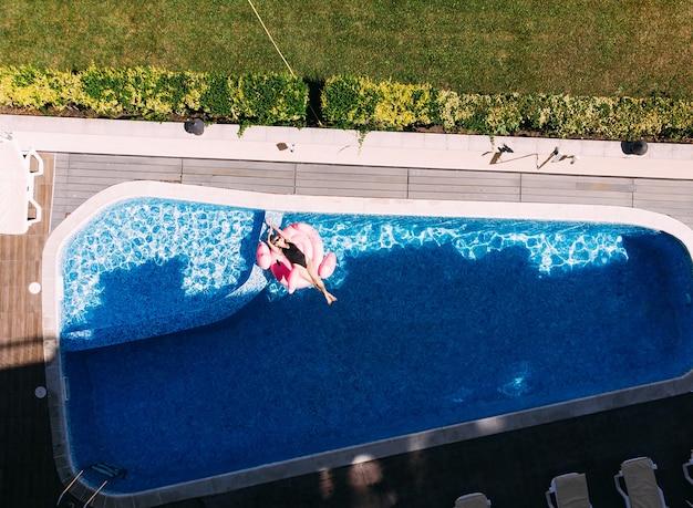 플라밍고 수영장에 있는 아름다운 여성이 호텔 수영장에 떠 있고 드론 공중 전망