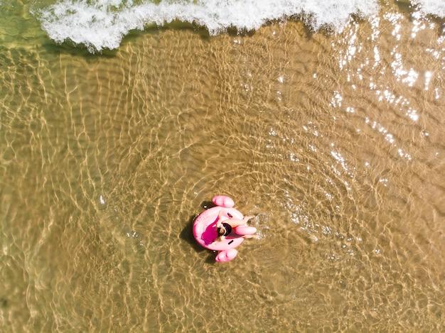 플라밍고 수영장에 있는 아름다운 여성이 바다의 수영장에 떠 있고 드론 공중 전망