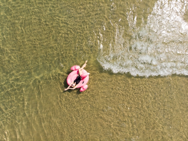 플라밍고 수영장에 있는 아름다운 여성이 바다에 떠 있고 드론 공중 전망