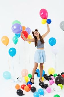 Красивая женщина на высоких каблуках выглядит счастливой, играя с воздушными шарами
