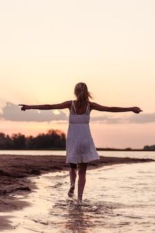 해변 후면 보기에 아름 다운 여자입니다. 하얀 드레스를 입은 가냘픈 젊은 금발이 일몰을 배경으로 강둑을 따라 손을 들고 달리고 있습니다.