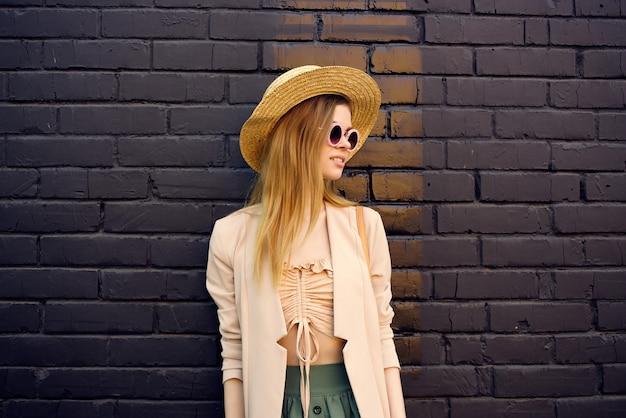 帽子と眼鏡を身に着けている通りの美しい女性黒レンガの壁の市内旅行。高品質の写真