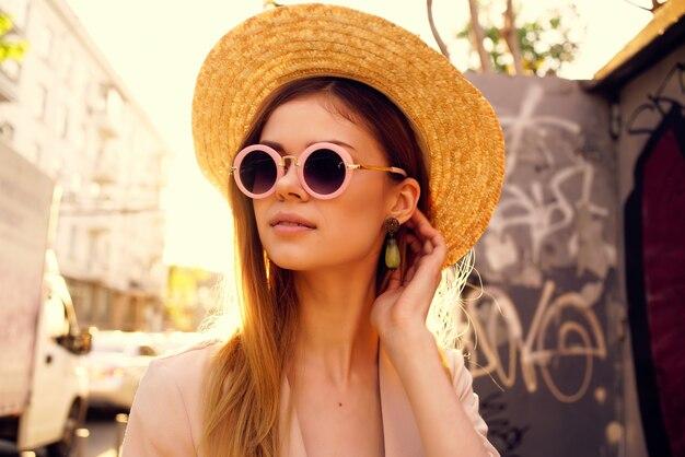 帽子とメガネのライフスタイルを身に着けている通りの美しい女性