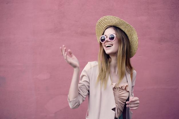 帽子とメガネのピンクの壁のモデルを身に着けている通りの美しい女性。高品質の写真