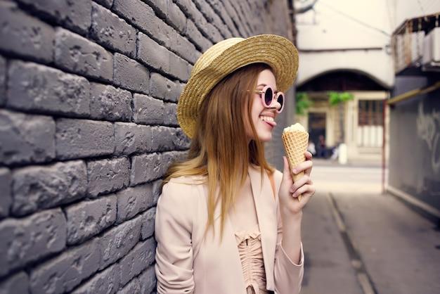 アイスクリームの休暇の市内旅行で通りの美しい女性。高品質の写真