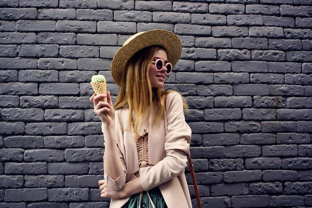 アイスクリームの休暇の市内旅行で通りの美しい女性