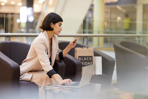 モールで美しい女性のオンラインショッピング