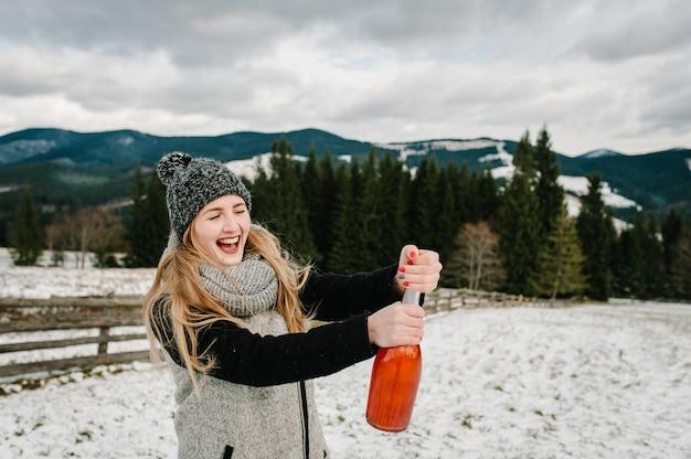 Красивая женщина открывает бутылку шампанского на фоне зимних гор. новогодние праздники. девушка снежной зимой, прогулка на природе. концепция путешествий и отдыха. сезон праздников.