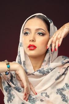 Beautiful woman in oriental style with mehendi on dark