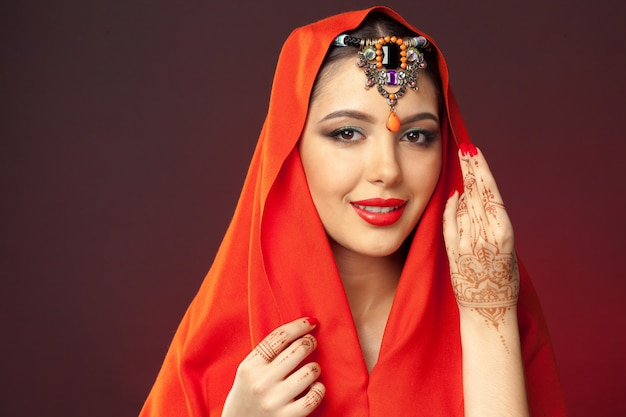 Beautiful woman in oriental style with mehendi on dark