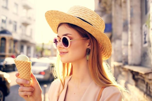 美しい女性の屋外散歩はアイスクリーム散歩旅行モデルを食べる