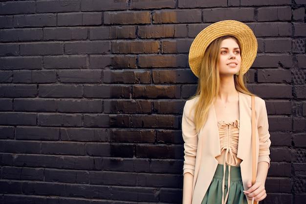 美しい女性の屋外散歩ファッション夏の黒レンガの壁