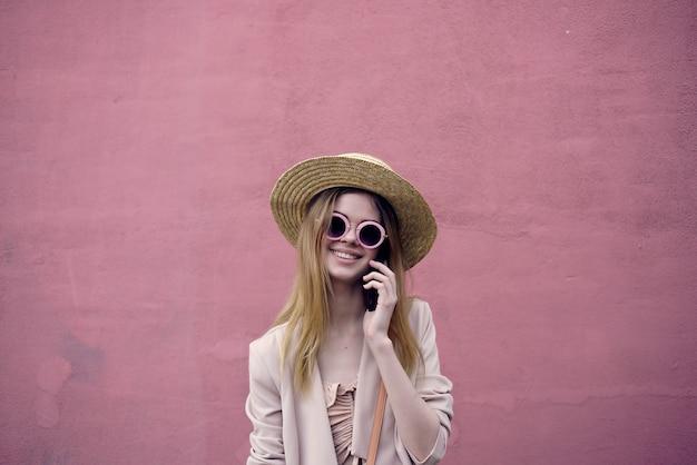 美しい女性の屋外散歩ファッション夏のピンクの壁のライフスタイル