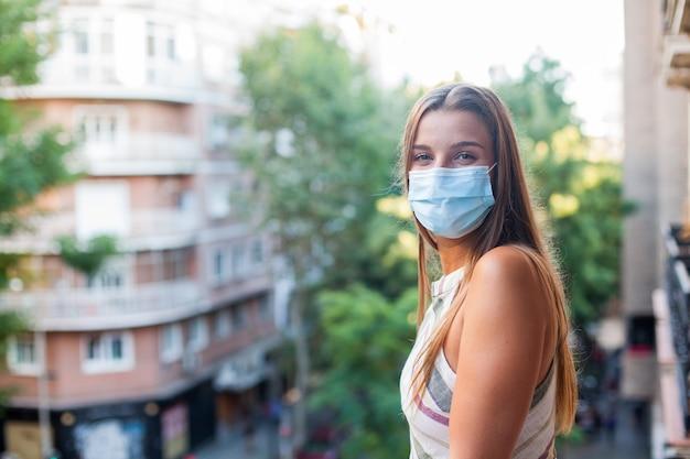 그녀의 테라스에서 보호 마스크를 쓰고 야외 아름 다운 여자