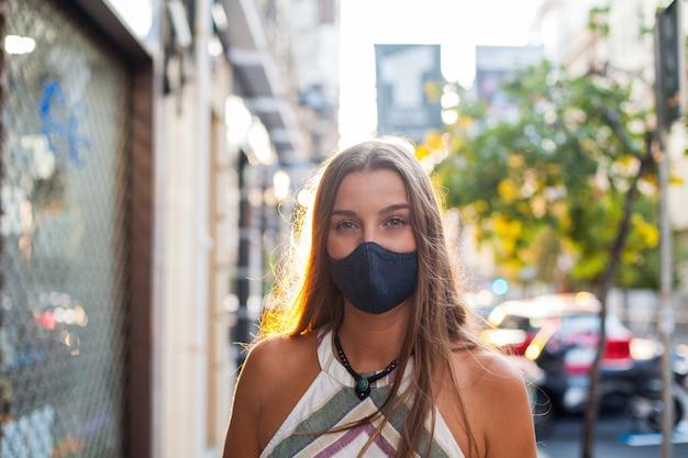 거리에 보호 마스크를 쓰고 야외 아름 다운 여자