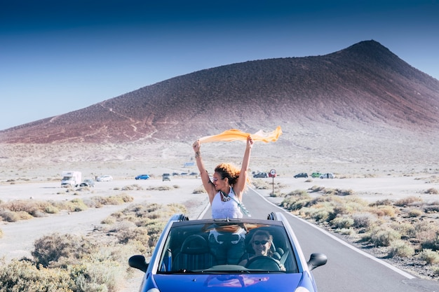 コンバーチブルの青い車の外の美しい女性は、自由を楽しんで、車を運転している彼女の女性の友人と一緒に道路で楽しんでいます